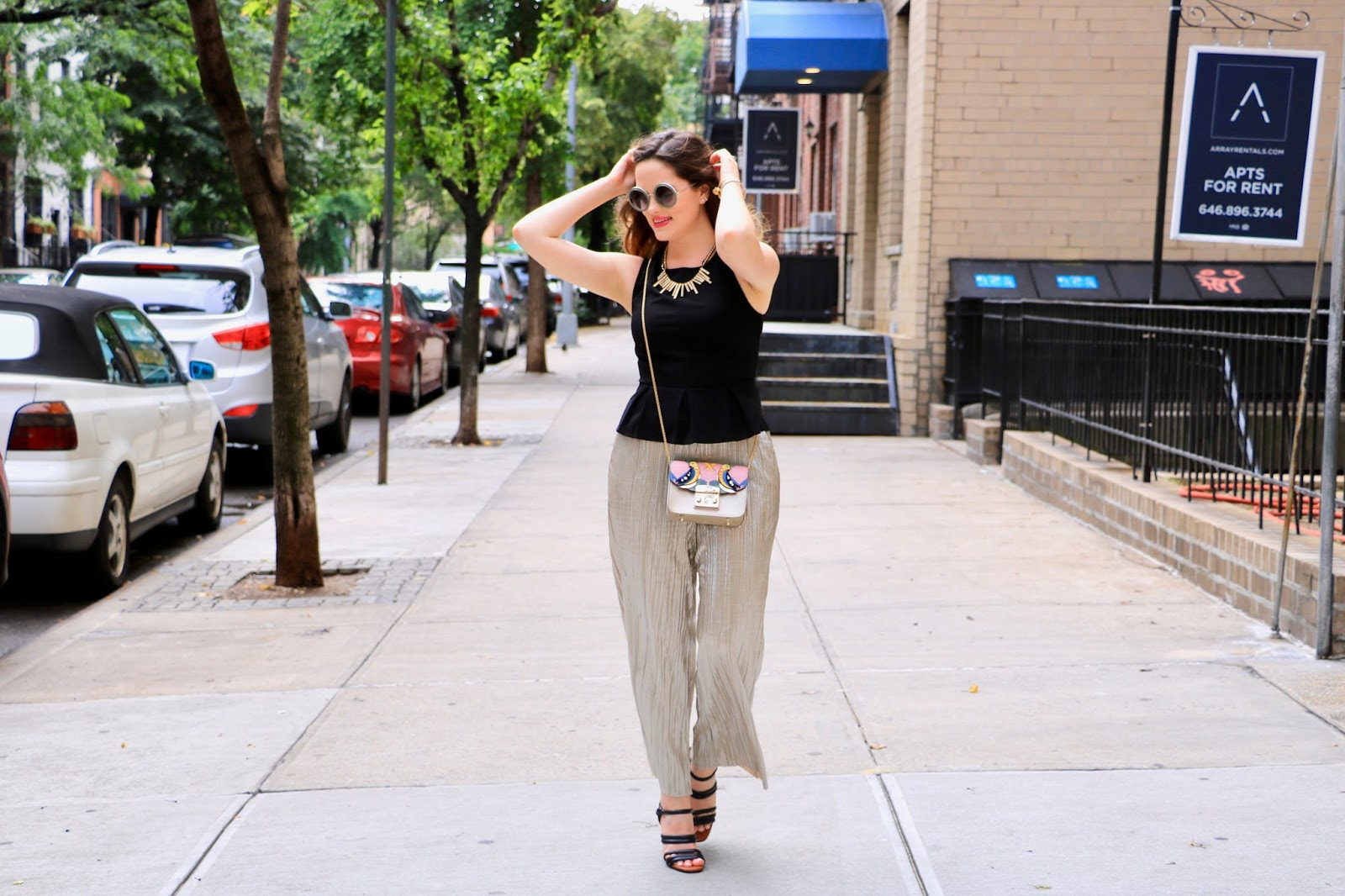 nyc fashion blogger Kathleen Harper wearing gold pants and a black peplum top with heels