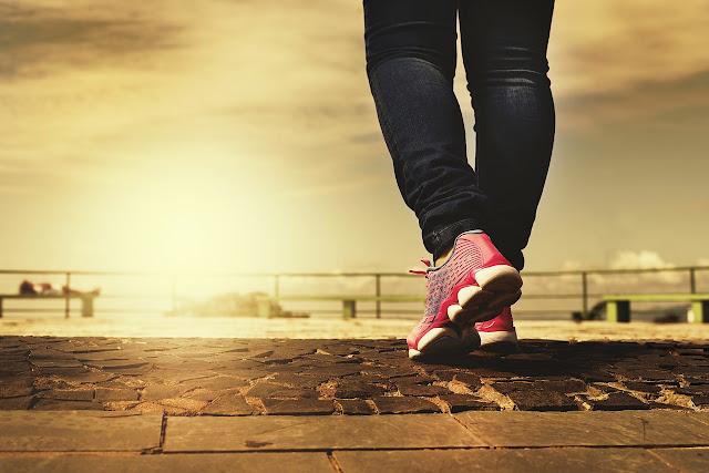 Die Beine eines Menschen  mit rosa Turnschuhen laufen dem Sonnenuntergang entgegen.