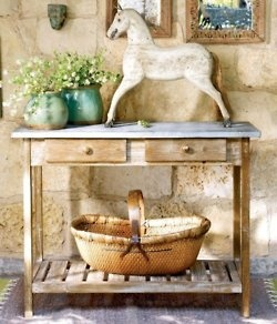 This rustic table is a relic in this french style kitchen scene