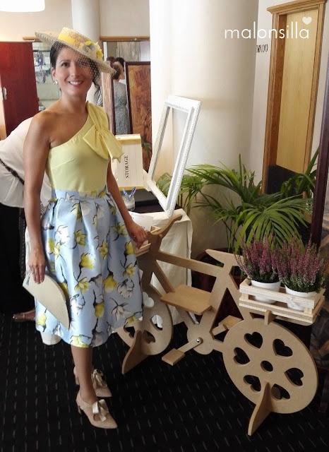 Invitada a boda con look en amarillo y azul celeste posando  junto a una bicicleta con plantas, lleva canotier y bolso by malonsilla