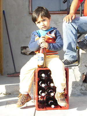 A young Peruvian boy familiarises himself with beer