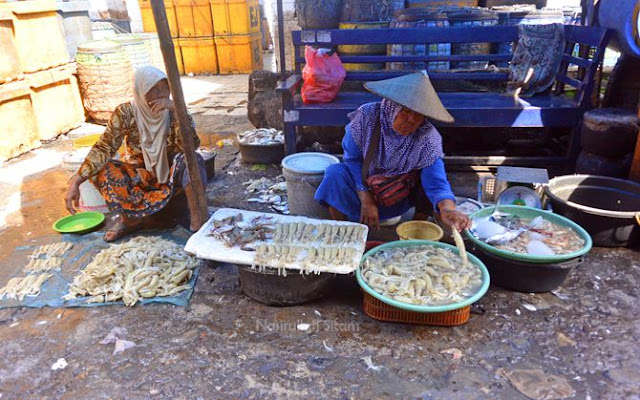 Ibu-ibu paruh baya menjual hasil laut dari nelayan