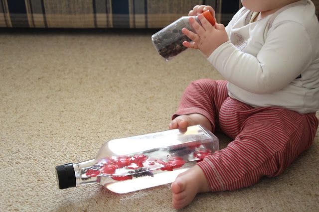 Baby shaking a discovery bottle full of gumnuts