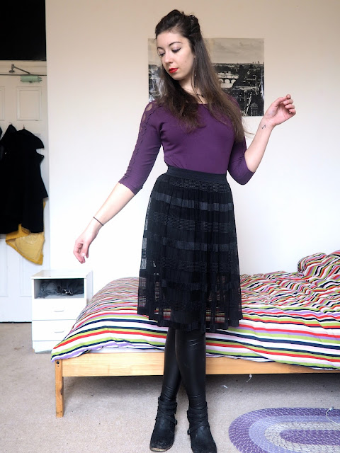 Ursula Disneybound outfit of purple lace sleeve top, black sheer skirt over leather effect leggings, and black ankle boots