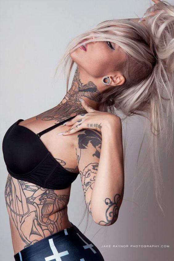 mujer de estilo punk, tira el cuerpo hacia atras, lleva tatuajes en las costillas