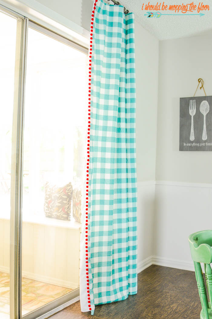 DIY Pom Pom Trimmed Drapes | These cheerful drapes were made with tablecloths and pom pom trim. Check out the entire tutorial to make these simple sew curtains.