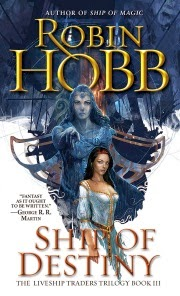 cover art for Ship of Destiny. A dark-haired woman of ambiguous ethnicity stands before a female figurehead in tones of blue. The woman wears a low-cut white dress edged in gold. The figurehead points and stares directly at the viewer.