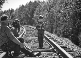 A depressed child walking on railway tracks as parents look on.