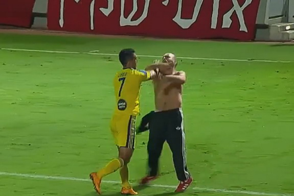 Maccabi Tel Aviv player Eran Zahavi fights with a Hapoel Tel Aviv supporter