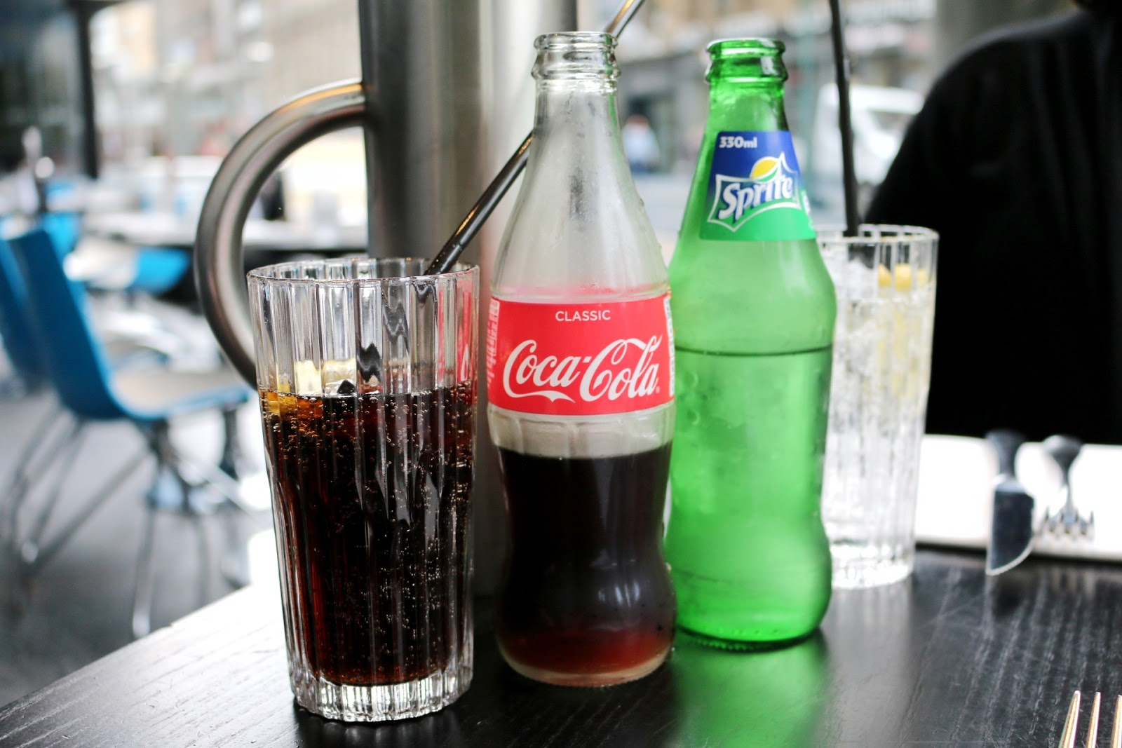 Close up of a bottle of coca-cola and a bottle of sprite. Both are glass bottles