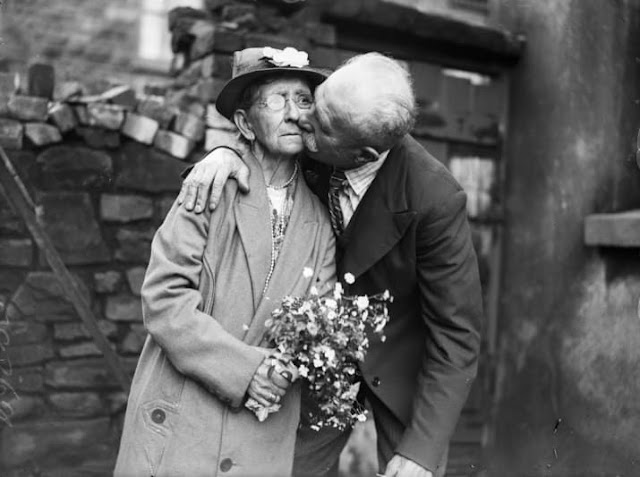 Vintage photo. An old couple. The man steals a kiss while she hold flowers.