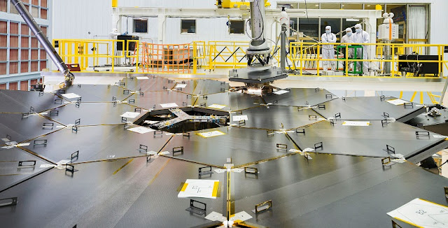 Inside a massive clean room at NASA's Goddard Space Flight Center in Greenbelt, Maryland the James Webb Space Telescope team used a robotic am to install the last of the telescope's 18 mirrors onto the telescope structure. Credits: NASA/Chris Gunn