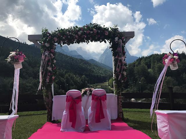 Blumenbogen zur freien Trauung, Pink travel themed wedding - Reise ins Glück Hochzeitsmotto im Riessersee Hotel Garmisch-Partenkirchen, Bayern Sommerhochzeit im Seehaus in den Bergen, Hochzeitsplanerin Uschi Glas