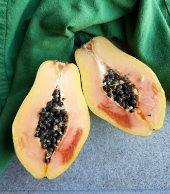 strawberry papaya cut in half with black seeds in center