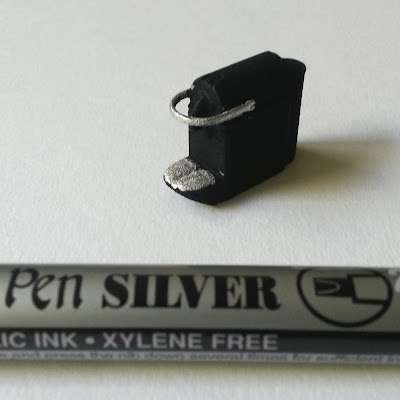 One-twelfth scale modern miniature 3D-printed Nespresso machine with silver highlights next to a silver caligraphy pen