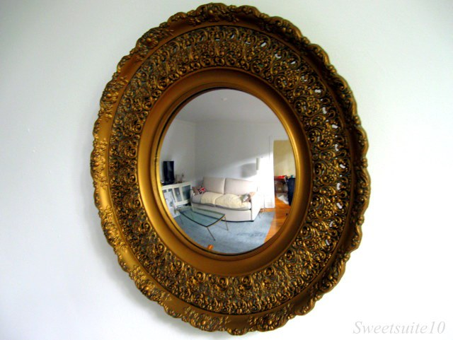 Convex mirror with gold coloured frame