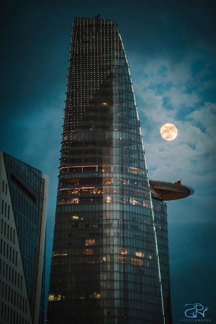 Mặt Trăng tỏa sáng sau những lớp mây mỏng cạnh một tòa nhà tại Quận 1, Sài Gòn. Hình ảnh: Nam Le Xuan Ha/SNB Fotos.