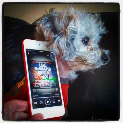 Murchie sits in profile, his attention fixed on something outside the right side of the frame. A pale hand holds a white iPod up against his ear. Its screen shows the cover of Gentleman Jole and the Red Queen, featuring red, green, and blue strands of chromosomes twining together in a triangle against the backdrop of space.