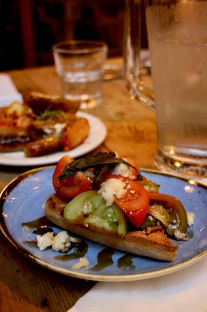 A plate of feta, heirloom tomato and watercress pesto on sourdough toast