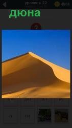 Под голубым безоблачным небом находится высокая дюна из желтого песка