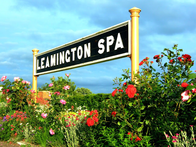 Photo of Old Leamington Spa former Great Western Railway platform sign surrounded by a myriad of station flowers