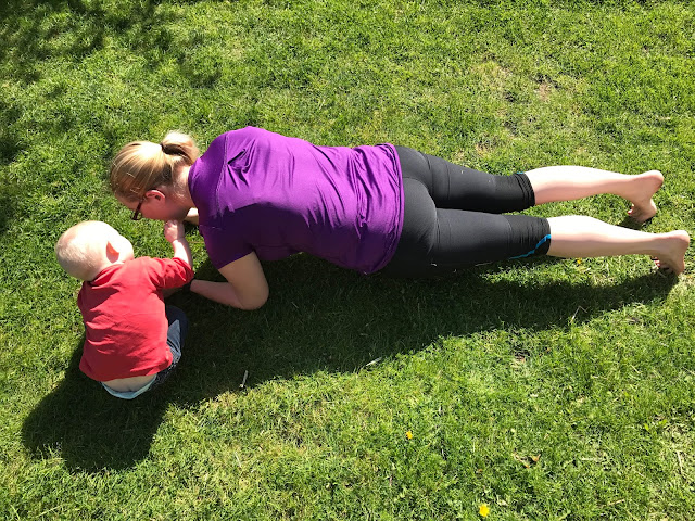 Doing a plank in the garden in a purple work out top and black leggings while my daughter pokes my face