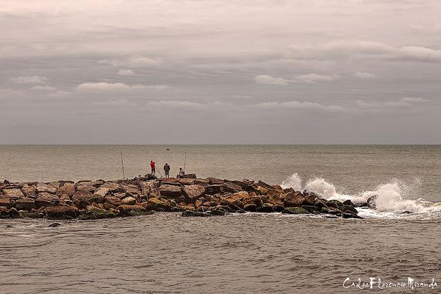 Sobre un espigón varios hombres pescando en el mar.