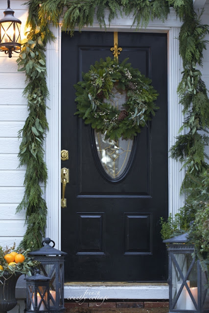 Black front door with greens and lanterns