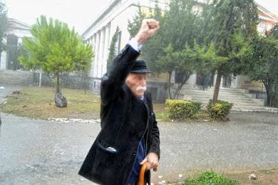 O Μανώλης Γλέζος στα 95 του,   έχει αψηφήσει την καταρρακτώδη βροχή.