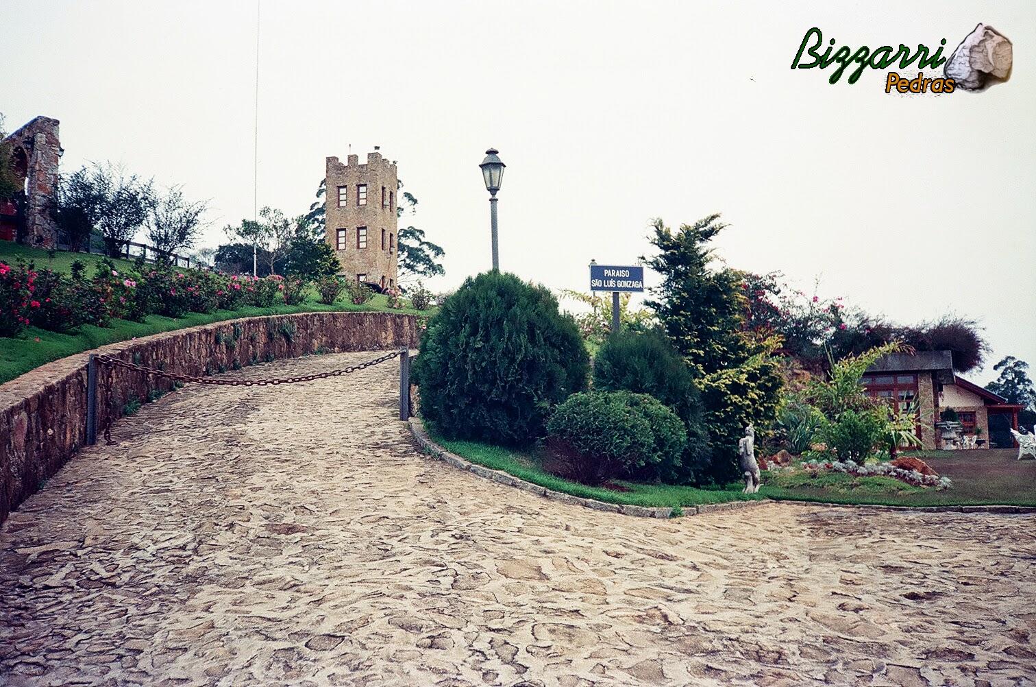 Na entrada do sítio em Mairiporã-SP o calçamento de pedra rústica com os muros de pedra, torre de pedra e o paisagismo.