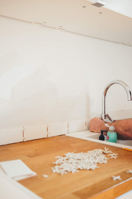 Image of a kitchen sink and counter top with someone tiling the splashback