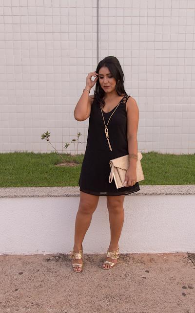 Vestido preto modelo trapézio com acessórios dourados
