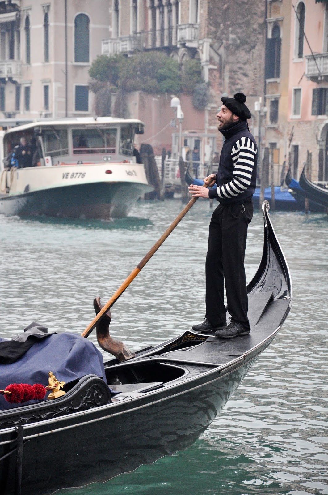 A gondolier and a vaporetto, Venice, Italy