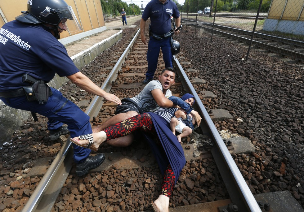 70 Of The Most Touching Photos Taken In 2015 - Hungarian policemen try to move a family of migrants off the tracks at a railway station in Bicske.