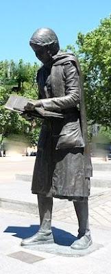 Escultura de la chica leyendo a la entrada del metro de Aluche. A sus pies una placa recuerda a Yolanda González