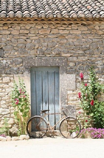 Decor inspiration & home decor ideas: #Frenchfarmhouse facade with limestone, weathered blue wood door, and vintage bicycle on Hello Lovely Studio