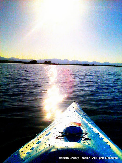 Sun glistens off the water's surface and the nose of the blue kayak.  The mountains all pale blue gray are at the horizon.