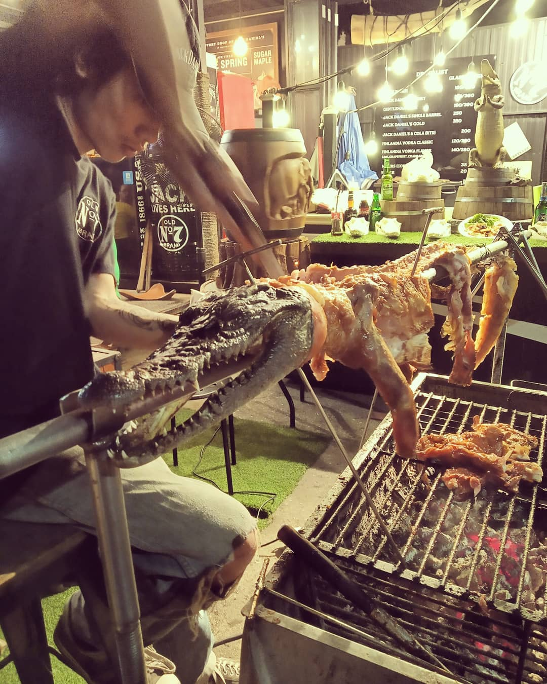 Guy carving crocodile meat on the spit