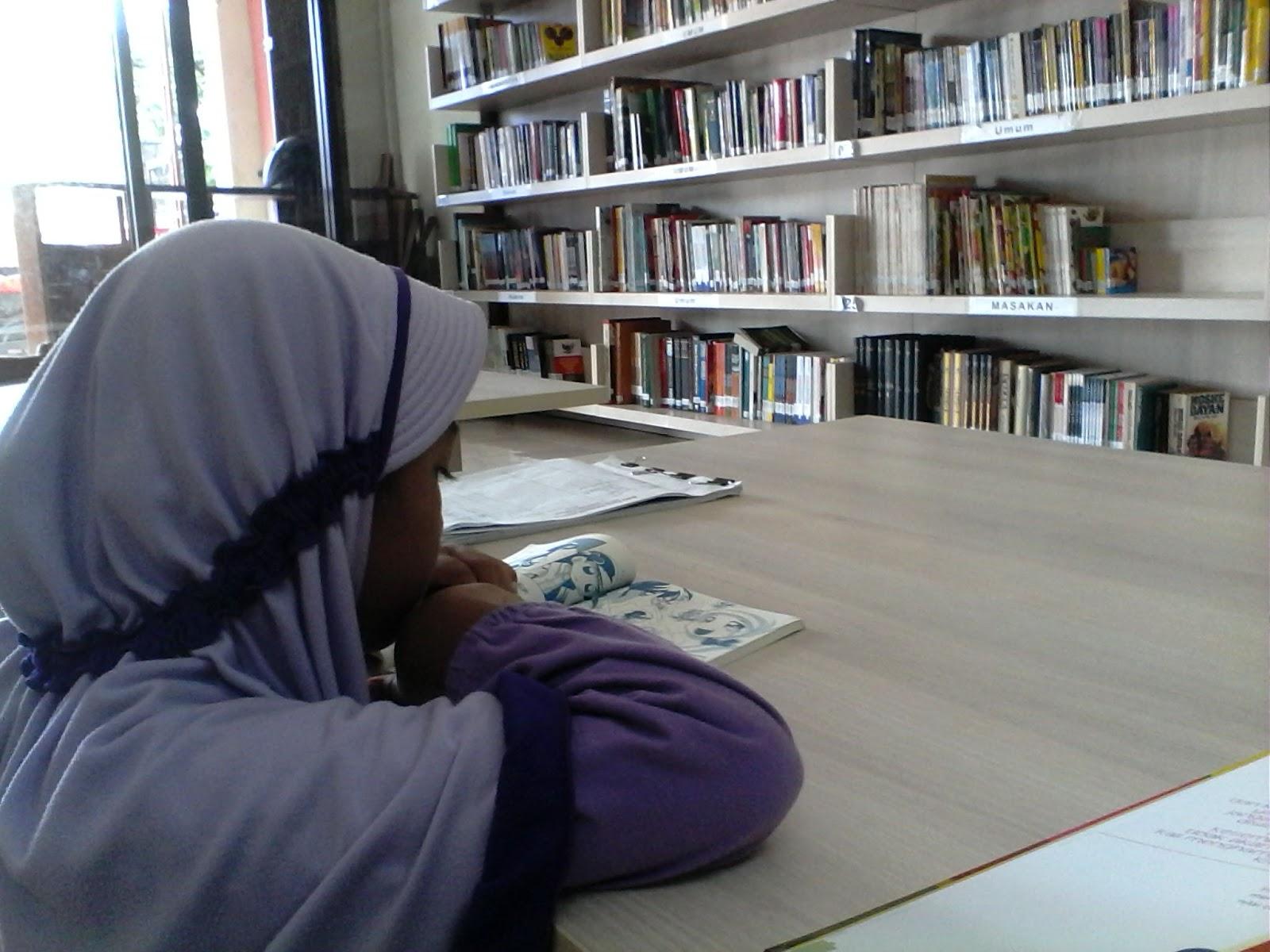 Syifa sedang asyik membaca buku di perpustakaan