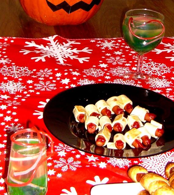 Tafel met Halloween-lekkernijen zoals vinger-worstebroodjes met ketchup, stomende limonade met groene glibbers en rozerode slierten en een versierde pompoen
