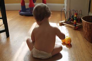 Kind spielt nur mit Windel bekleidet