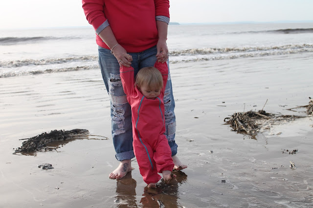 Mother & baby walking in the sea wearing matching colour clothing
