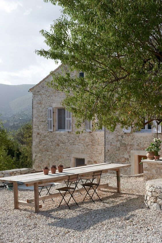 Picture perfect #Frenchfarmhouse stone house with blue shutters and outdoor dining area on Hello Lovely Studio