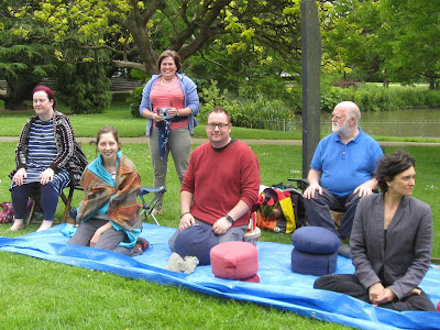 Group getting ready to meditate in the park