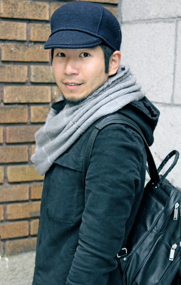 Montrealer Man in Japanese Student style, wearing black long cotton hoodie coat designed by Stephan Schneider and dark navy blue wool cap hat