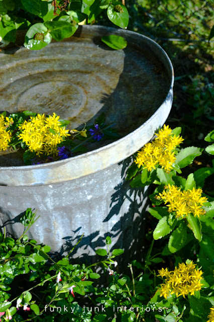 A garbage can birdbath via Funky Junk Interiors