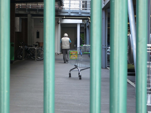 A woman walks through bleak, barred area where there are shopping trolleys and bikes.