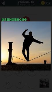 Мужчина идет на проволоке и пытается соблюдать равновесие