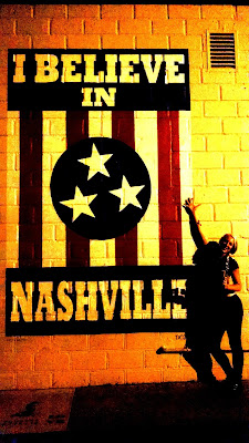 "Skipper standing in front of a piece of art that says ""I BELIEVE IN NASHVILLE"""