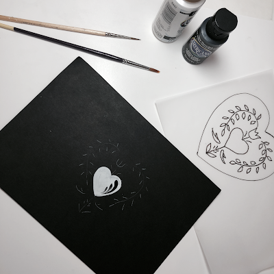 Black paper with a traced design and painted heart next to a folk art pattern on tracing paper